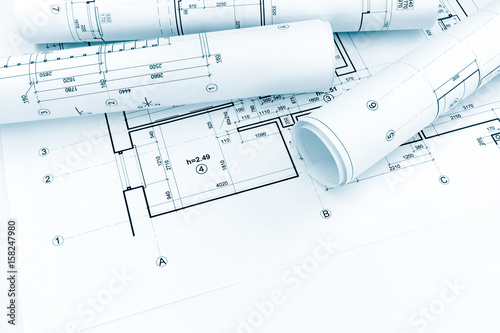 Rolled Architectural Plans And Technical Drawings On House Blueprint