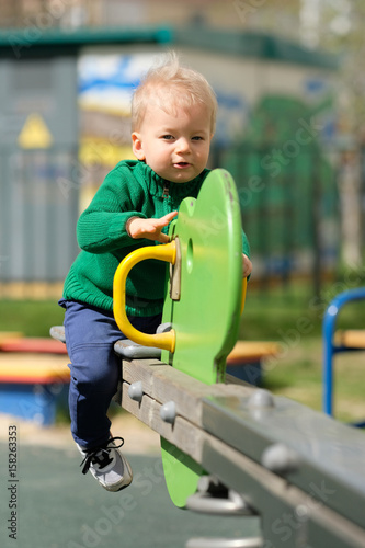 Papiers peints Attraction parc One year old baby boy toddler wearing green sweater at playground