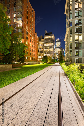 Highline promenade and old railway tracks at twilight with high-rises and building lights in Chelsea Poster