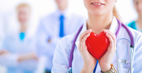 Female doctor with stethoscope holding red heart