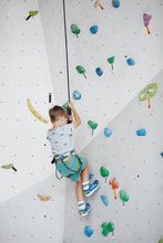 Child Climbing On A High Wall