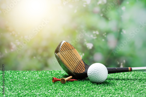 Poster Golf golf club ball and tee on fake grass against morning sunlight behind the bush at back