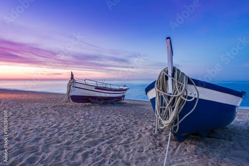 Foto op Aluminium Strand Fishing boat on sandy beach at nostalgic sunrise