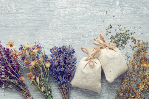 Photo  Bunches of of healing herbs and and sachet on gray wooden board