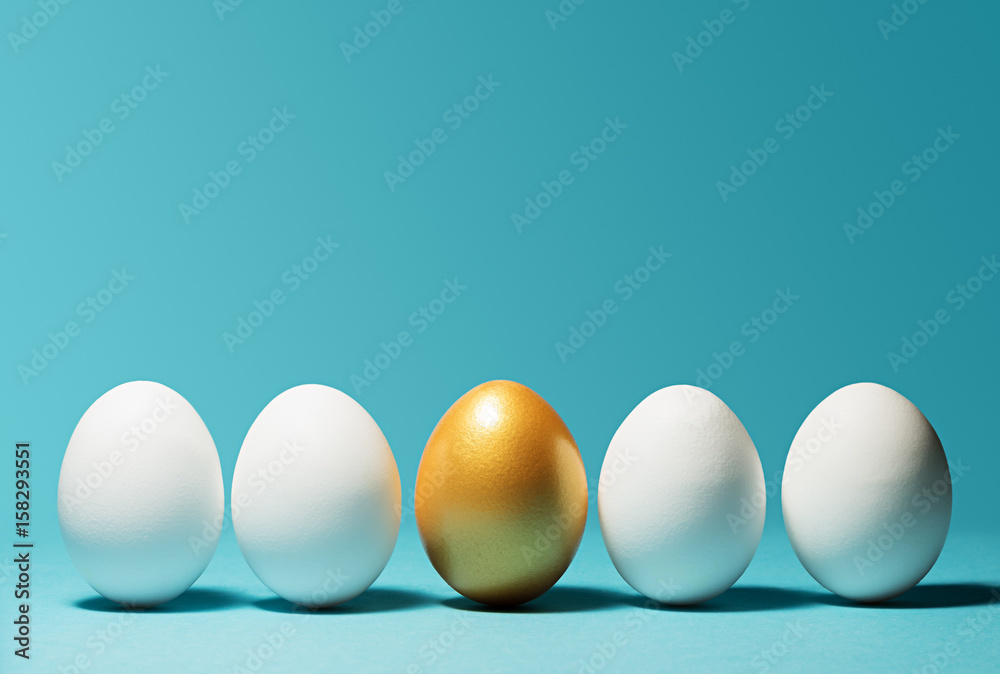 Fototapety, obrazy: Concept of individuality, exclusivity, better choice. One golden egg among white eggs on blue background.