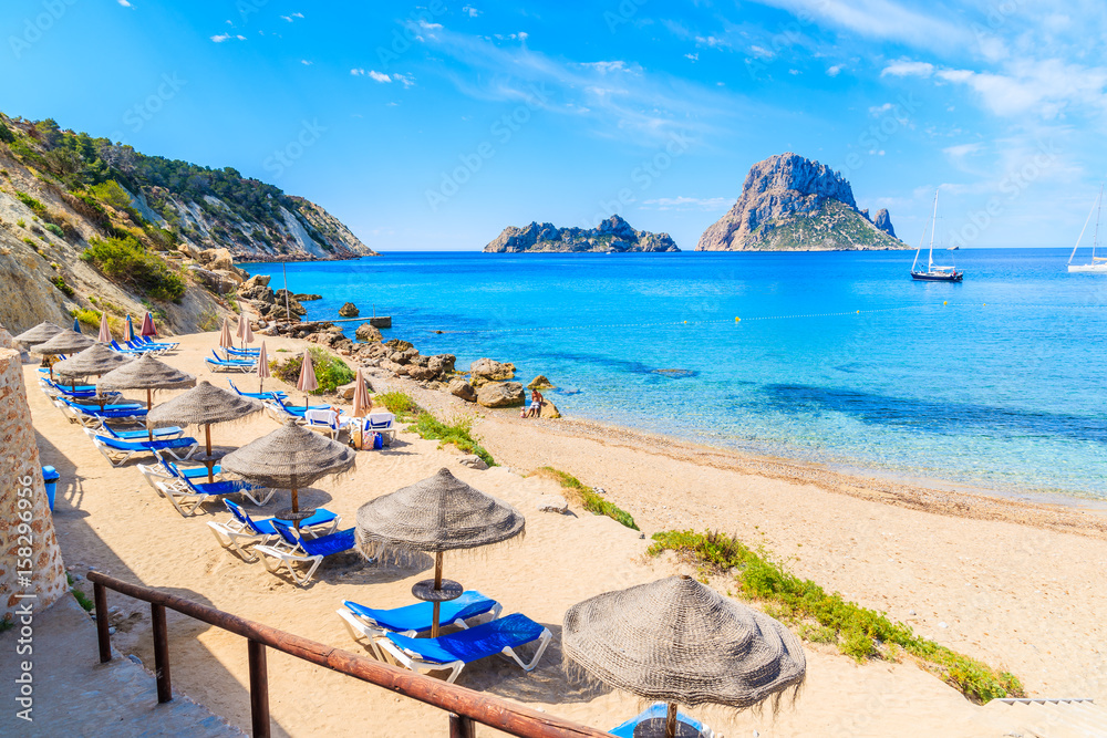 Fototapety, obrazy: View of Cala d'Hort beach with sunbeds and umbrellas and beautiful azure blue sea water, Ibiza island, Spain