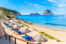 View Of Cala D'Hort Beach With Sunbeds And Umbrellas And Beautiful Azure Blue Sea Water, Ibiza Island, Spain