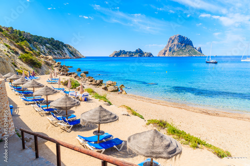 View of Cala d'Hort beach with sunbeds and umbrellas and beautiful azure blue se Fotobehang