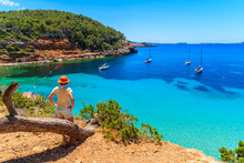 Young Woman Tourist Standing On Rock Cliff Edge And Looking At Beautiful Cala Salada Bay Famous For Its Azure Crystal Clear Sea Water, Ibiza Island, Spain