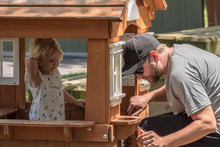 Father And Daughter In Playhouse In Backyard