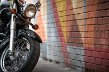 Closeup Of Motorcycle's Wheel On Bright Colorful Graffiti Background. Modern Motorcycle Standing At The Brick Wall In The City.