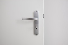 Metal Door Handle With Key On White Door