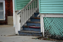 Peeling And Decaying Steps Of Old Wooden House In Urban Neighborhood