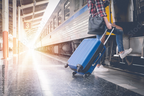 Photographie Alone traveler wait suitcases waiting for her train on platform of railway train station in summer