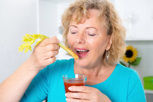 Young Woman And Her Mother Drinking Tomato Juice Together In The