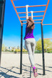 Young beautiful brunette girl in blue t-shirt climbing a horizontal ladder in the park.