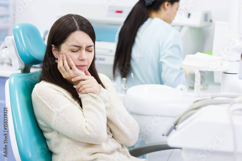 Fotografia  Unhappy patient having a toothache in dental clinic