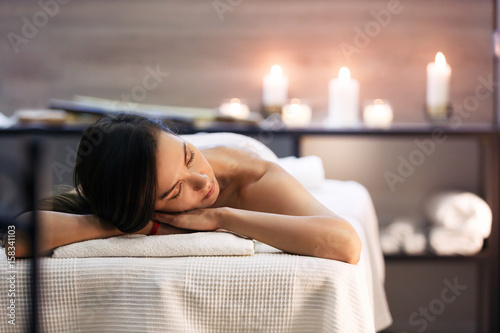 Poster Spa Beautiful girl in spa salon on candle background