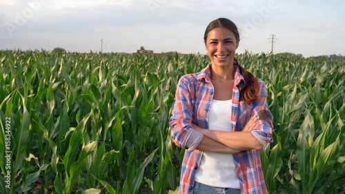 Pinturas sobre lienzo  Beautiful girl (woman) farmer smiling, looking, checking cornfield, young tanned, green background