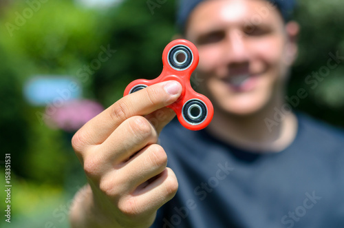 Fotografie, Obraz  young man playing with a fidget spinner