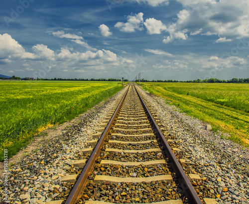 Deurstickers Spoorlijn railroad track in open green field, summer time traveling, freedom of movement