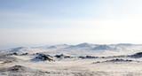 Wczesnym rankiem wschód słońca na stepach Tazheran. Pokryte śniegiem wzgórza są barwione w odcieniach ultrafioletu. Zdjęcie stonowane. - 158364310