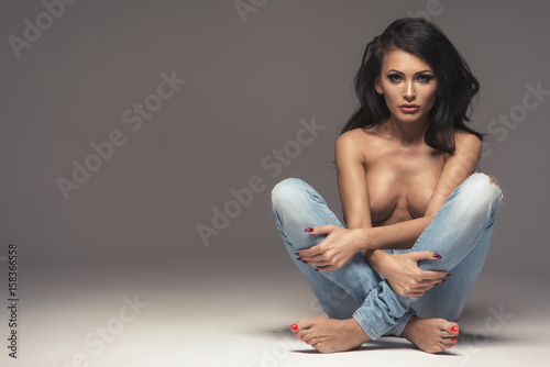 Obraz Sexy attractive brunette woman posing only in jeans in studio - fototapety do salonu