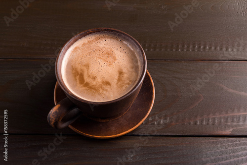 Foto op Plexiglas Chocolade Hot chocolate or cocoa drink in clay cup, on dark brown wooden table