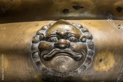 Tuinposter Boeddha Brass face on incense pot,Temple in Thailand.