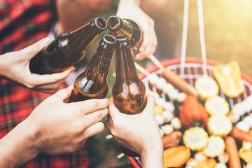 Friends clinking bottle of beer during camping outdoor with barbecue in backg...