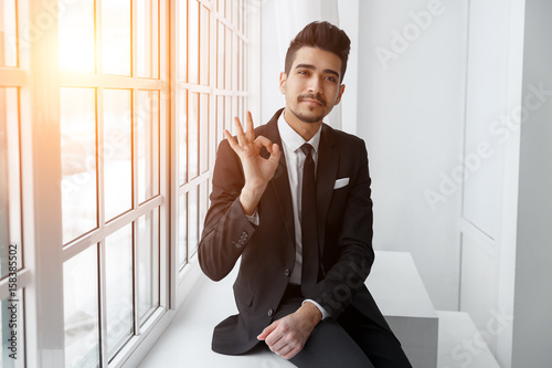 Fototapety, obrazy: Happy young businessman showing ok sign over office background