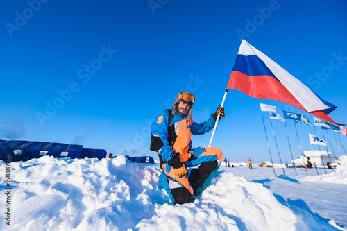 Photo sur Toile Nautique motorise Close-up of a man in a Colorful down jacket Fur cap Beard and mustache in a frost in the background of the camp Barneo on a With the Russian flag snowy north pole in winter polar explorer