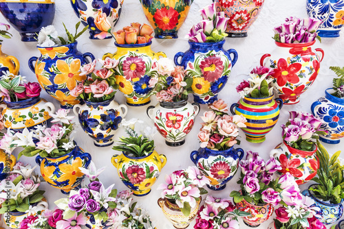 Photo Colourful ceramic vases with flowers on a shop wall at Mijas