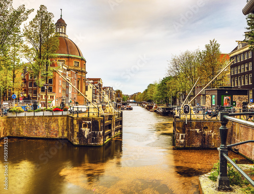 Obrazy na płótnie Canvas AMSTERDAM, NETHERLANDS - MAY 25, 2017: The most famous canals and embankments of Amsterdam city during sunset. General view of the cityscape and traditional Netherlands architecture.