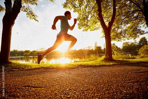 Plakat człowiek działa szybko w parku podczas zachodu słońca