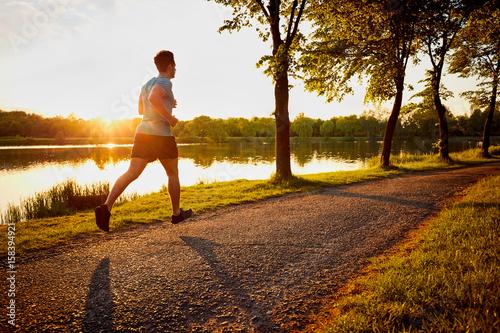 Plakat Młody człowiek jogging w parku podczas zmierzchu