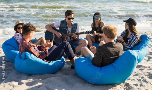Plakat grupa przyjaciół z gitarą na imprezie na plaży - młodzi ludzie hipster na wakacje siedzi na torby fasoli i gra na gitarze w pobliżu morza