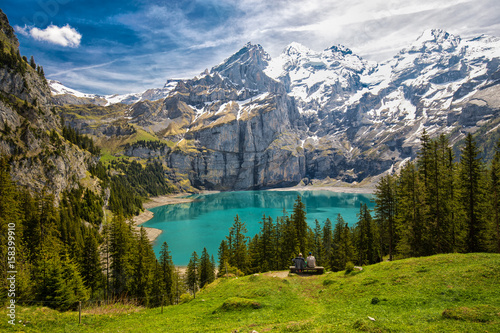 Fotobehang Alpen Amazing tourquise Oeschinnensee with waterfalls, wooden chalet and Swiss Alps, Berner Oberland, Switzerland.