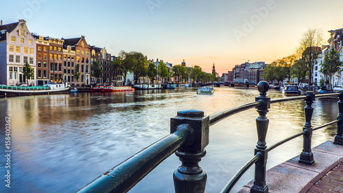 Cadres-photo bureau Amsterdam The most famous canals and embankments of Amsterdam city during sunset. General view of the cityscape and traditional Netherlands architecture.