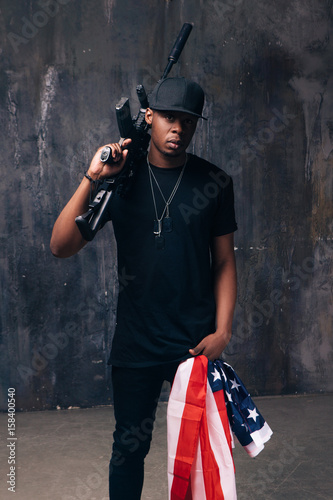 Fotografía  Armed confident black man with american flag and weapon stay on dark background