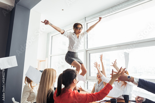 Photo  picture of happy business team celebrating victory in office