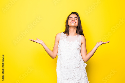 Fotografie, Obraz  Happy woman keeping hands raised over yellow wall