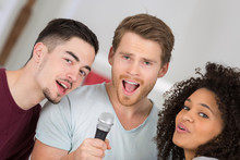 Three Young People Singing Int...