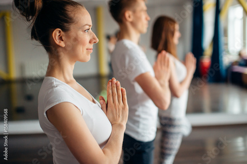 Yoga group concept. Young man and womans meditating together