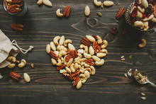 Nuts Mix In Heart Shape On The Wooden Table. Nuts Mix With Seeds And Dried Fruits On The Wooden Table