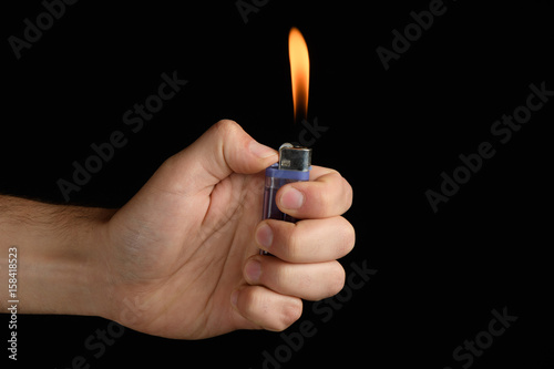 Photo  male hand holding a purple lighter with a large flame on a black background
