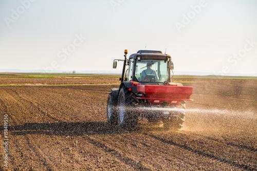 Zdjęcie XXL Rolnik nawożący ziemię uprawną za pomocą azotu, fosforu, nawozu potasowego