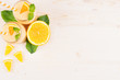 Orange citrus smoothie in glass jars with straw, mint leaf, cut orange, top view. White wooden board background, copy space.