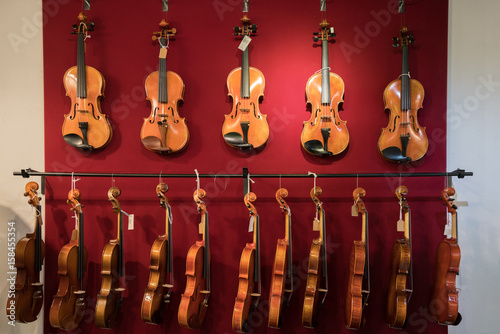 Photo Stands Music store Violins are hanging on the red wall in the shop.
