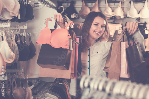 female customer showing her purchases in underwear shop - Buy this ... 22b7f8b27